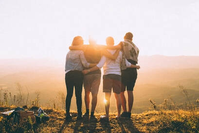 A group of four people embracing and watching the sun set.